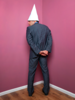 Man standing facing corner of room wearing a dunce cap